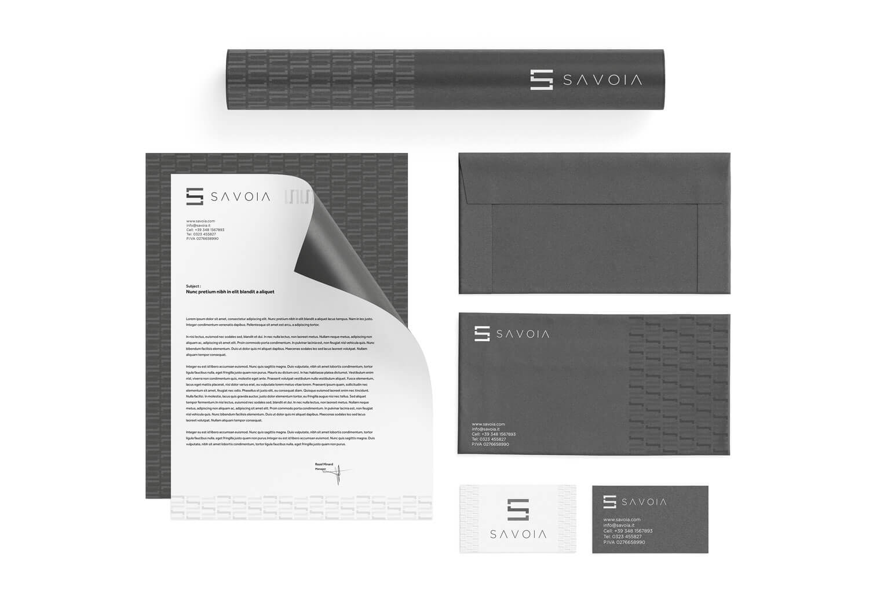 carta intestata bianca, due buste grigie e due biglietti da visita con logo e brand identity design di Savoia visti dall'alto su sfondo bianco