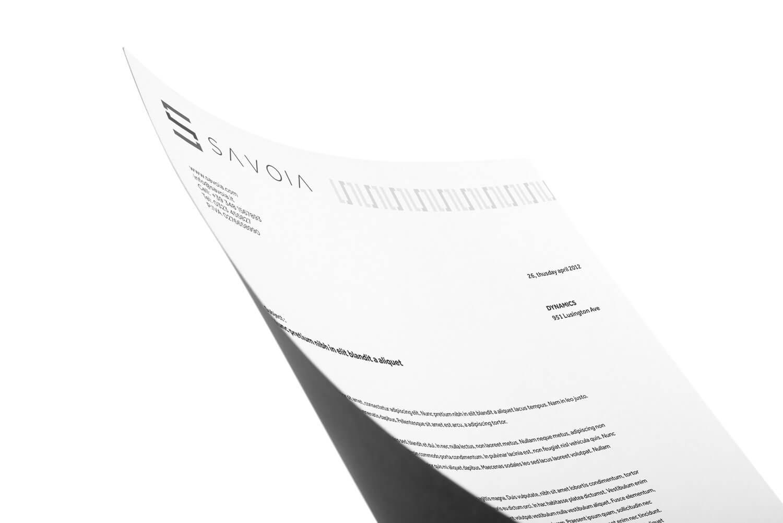 macro inquadratura di una carta intestata bianca con retro grigio con il logo e brand identity design di savoia su sfondo bianco