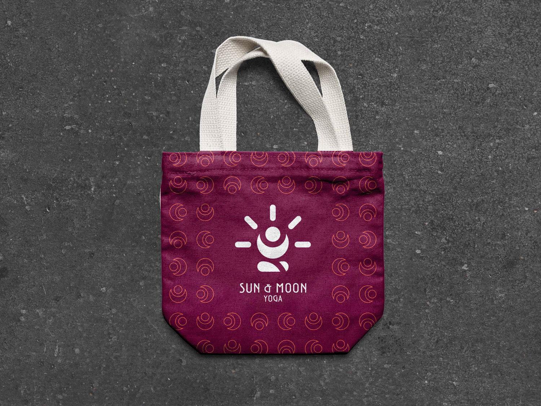 borsa di stoffa di colore viola con manici bianchi con il logo e brand identity design di Sun & Moon Yoga fotografata dall'alto sull'asfalto