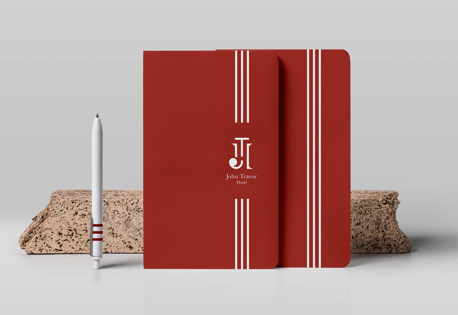 logo e brand identity design di john travor hotel su agenda e penna appoggiati su un marmo beige su sfondo grigio