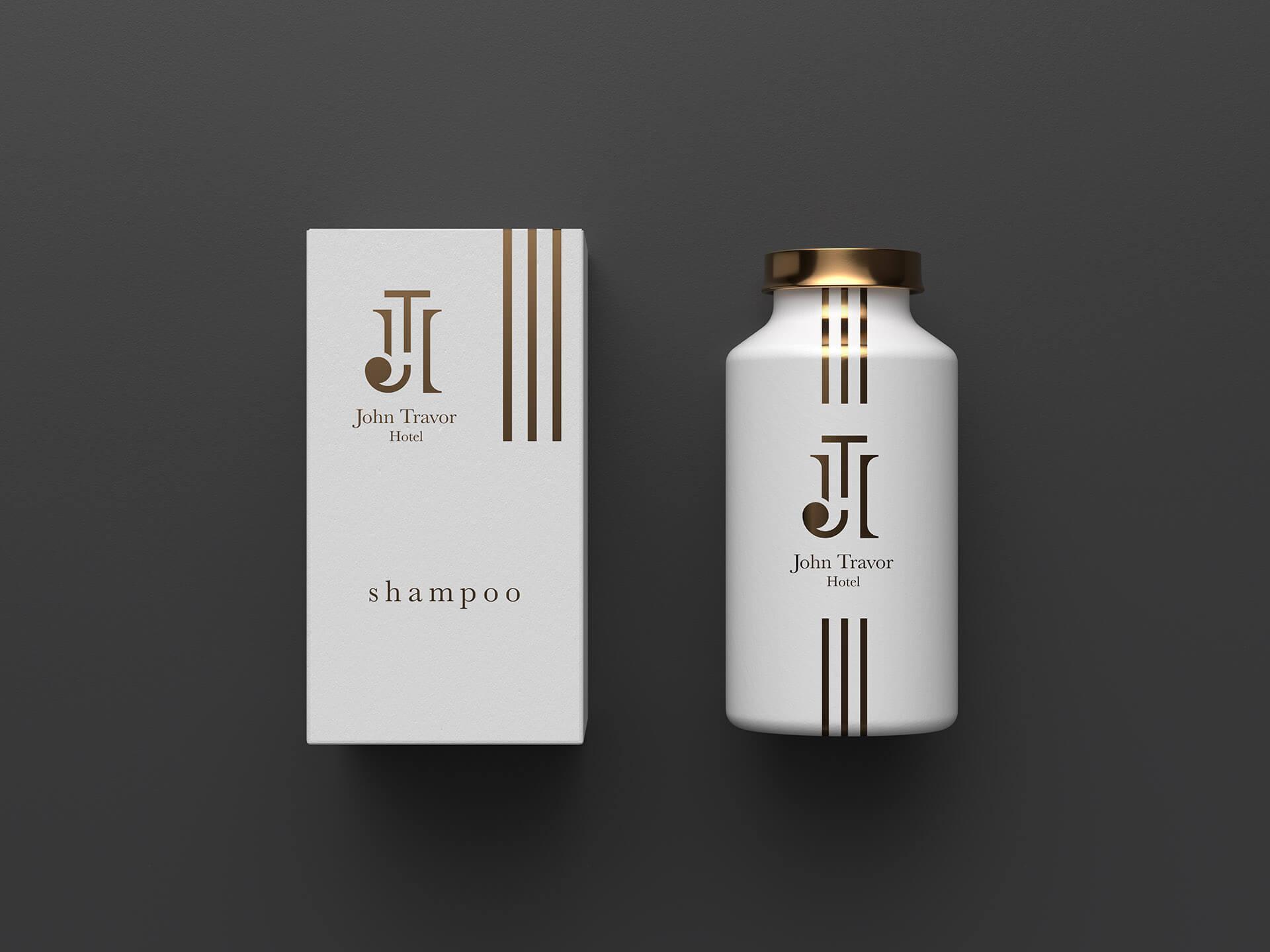 logo e brand identity design di john travor hotel su due confezioni di shampoo di colore bianco su sfondo grigio scuro