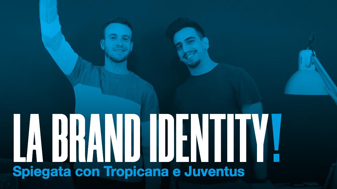 LA BRAND IDENTITY scritto in bianco con punto esclamativo blu con una foto di sfondo di due ragazzi con filtro blu