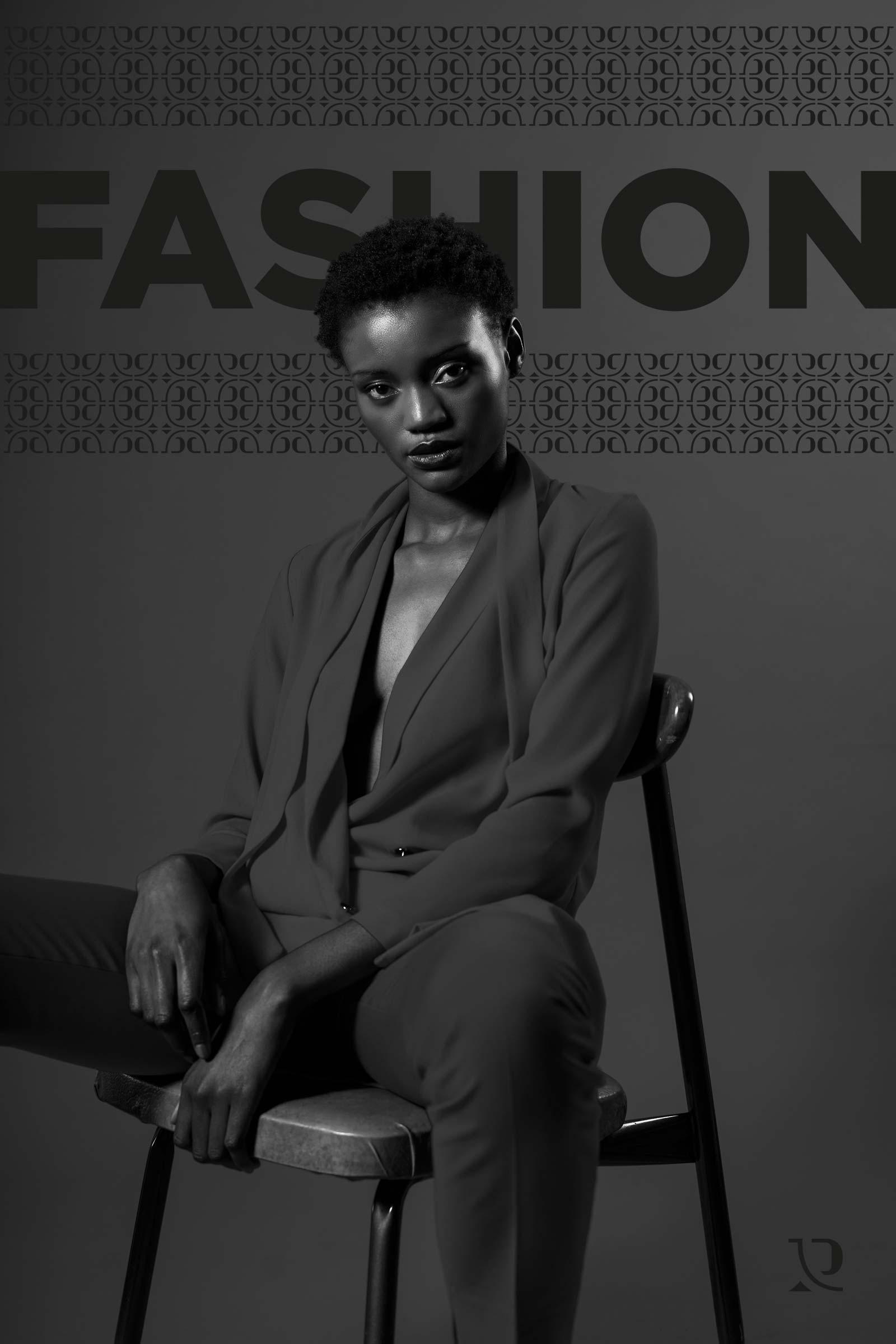 """Modella di colore con vestito grigio su sfondo nero. Sullo sfondo è presente anche la scritta nera """"FASHION"""""""