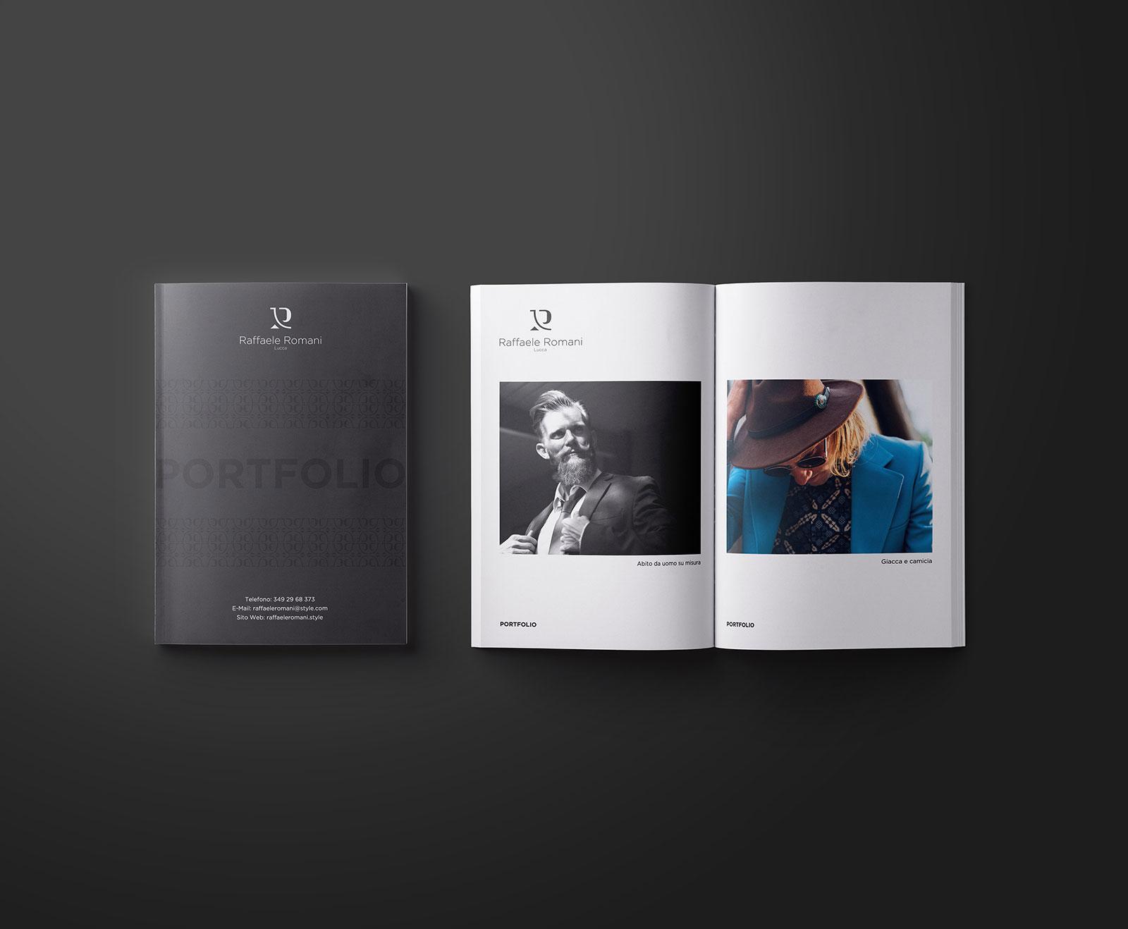 """Libro con la copertina nera con scritto """"PORTFOLIO"""" con pagine bianche che mostrano i vestiti. Il libro è su sfondo nero."""