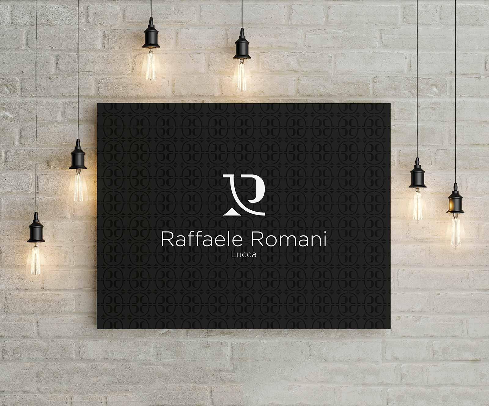 Quadro di colore nero con il logo di Raffaele Romani bianco al centro. Il quadro è posto su una parete di sassi con intorno delle lampadine