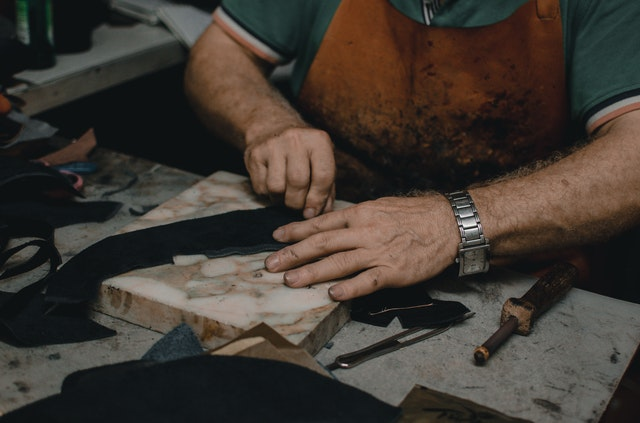 A man sewing leather