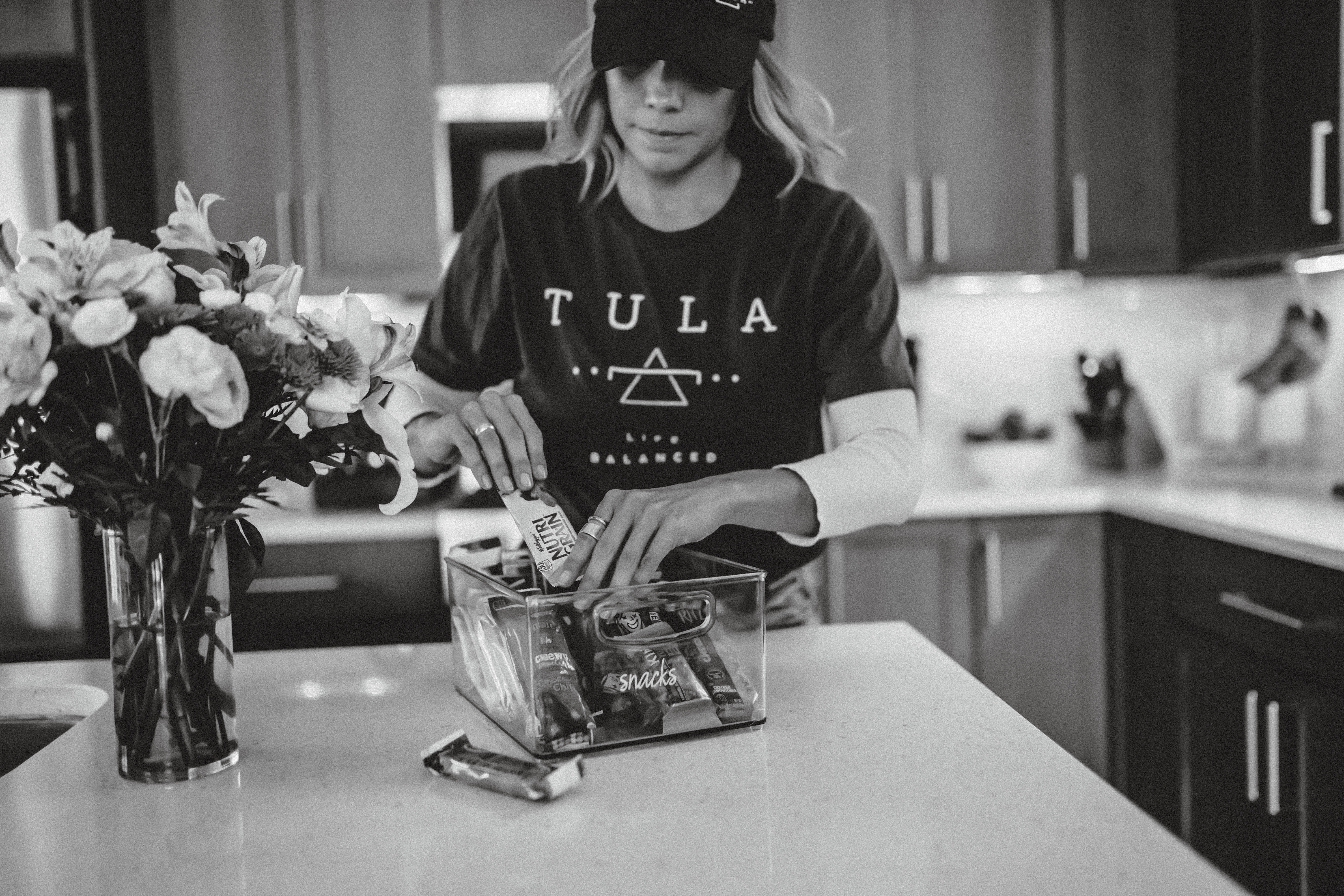 TULA Assistant wears TULA shirt and hat as she organizes a snack clear container on a white countertop next to a vase of flowers