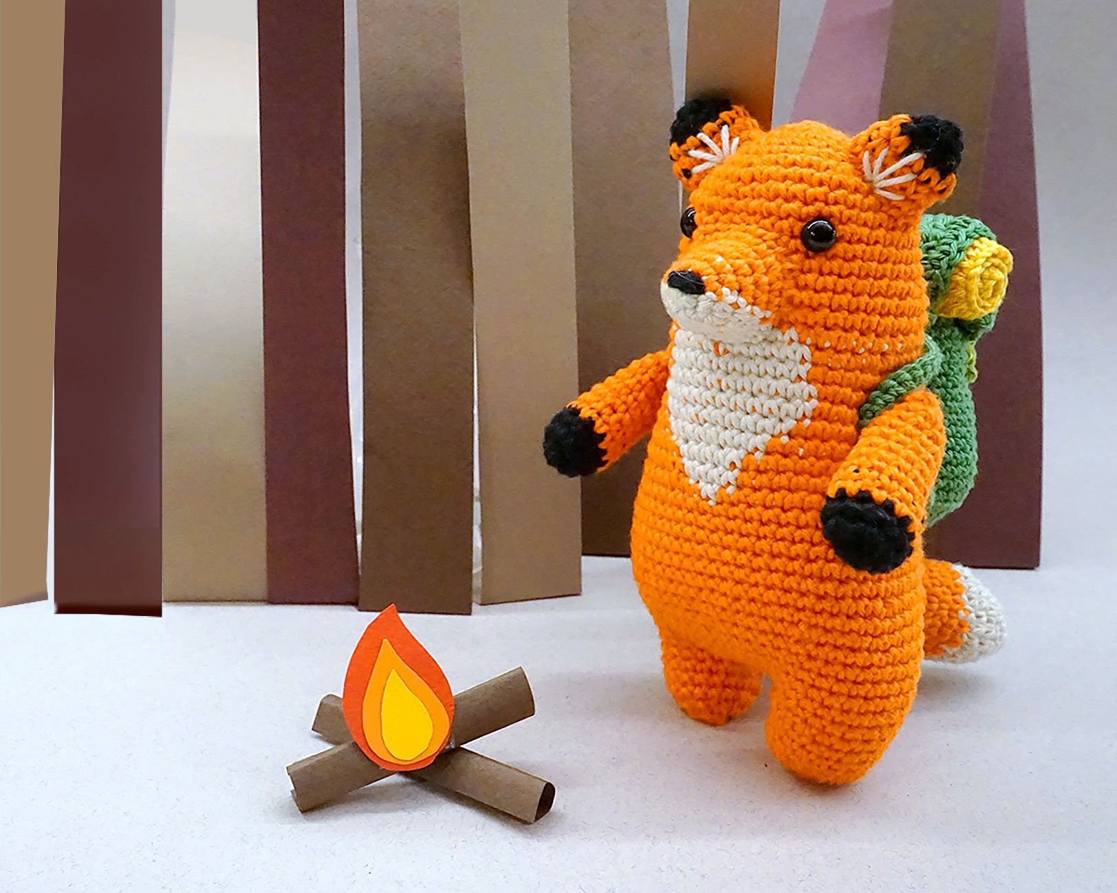 A Wooble, a crocheted fox with a backpack, standing next to a paper fire.