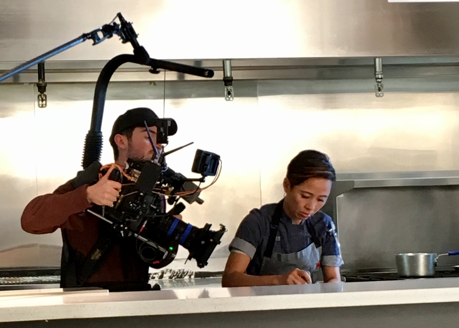 A man holding a large camera, filming Monica of Little Green Cyclo in a kitchen cooking.