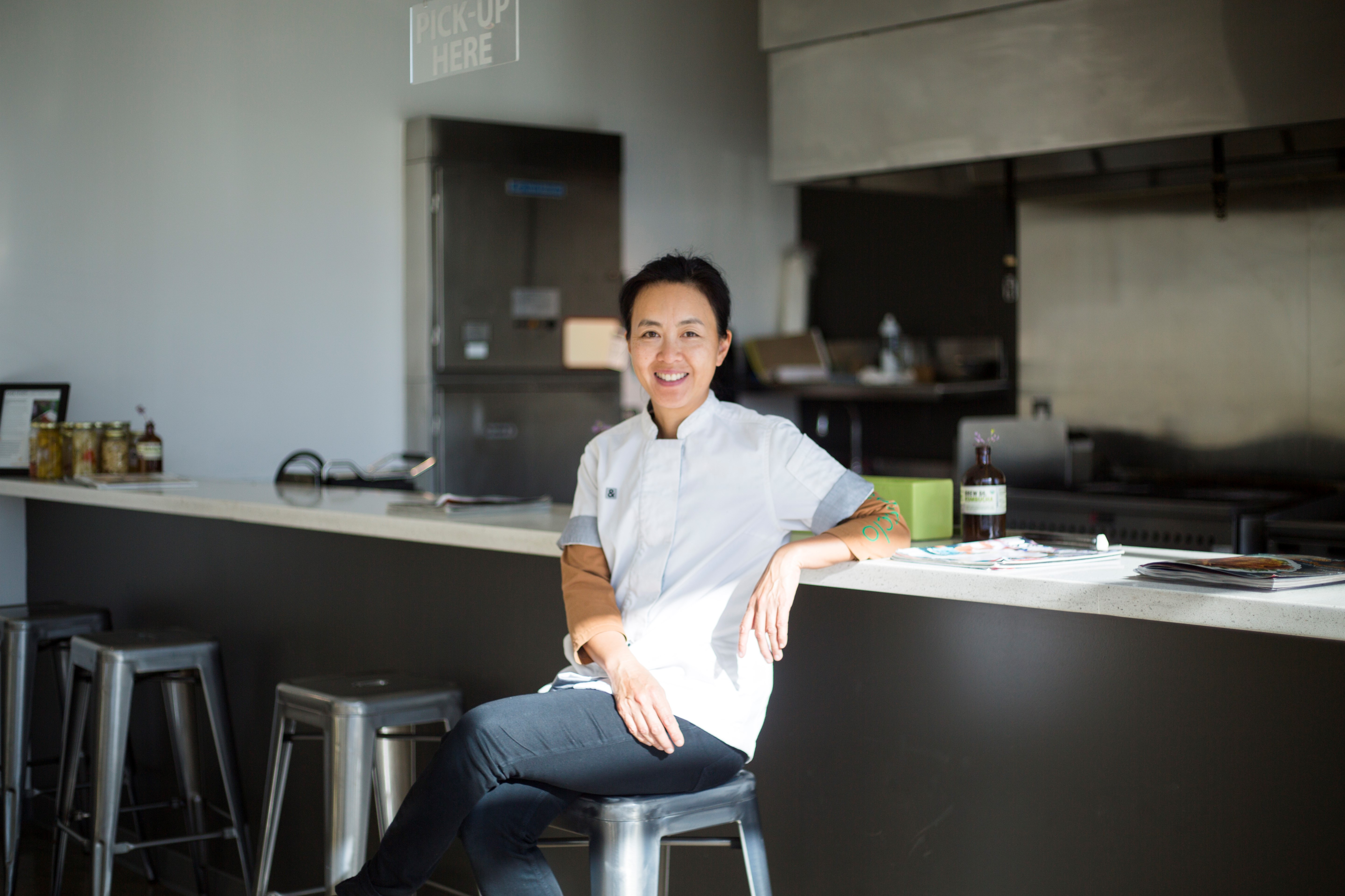 CEO of Little Green Cyclo, Monica Wong, sitting on a stool in a restaurant smiling.