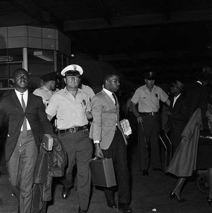 Police officers arresting Charles Butler and John Lewis after the Freedom Riders arrived at the Greyhound station in Birmingham, Alabama.