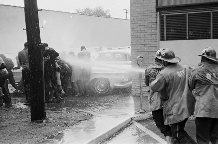 Firemen spraying civil rights demonstrators with a hose during a protest in downtown Birmingham, Alabama.