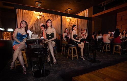 Thai girls sitting on stools around a VIP table at The PIMP Bangkok