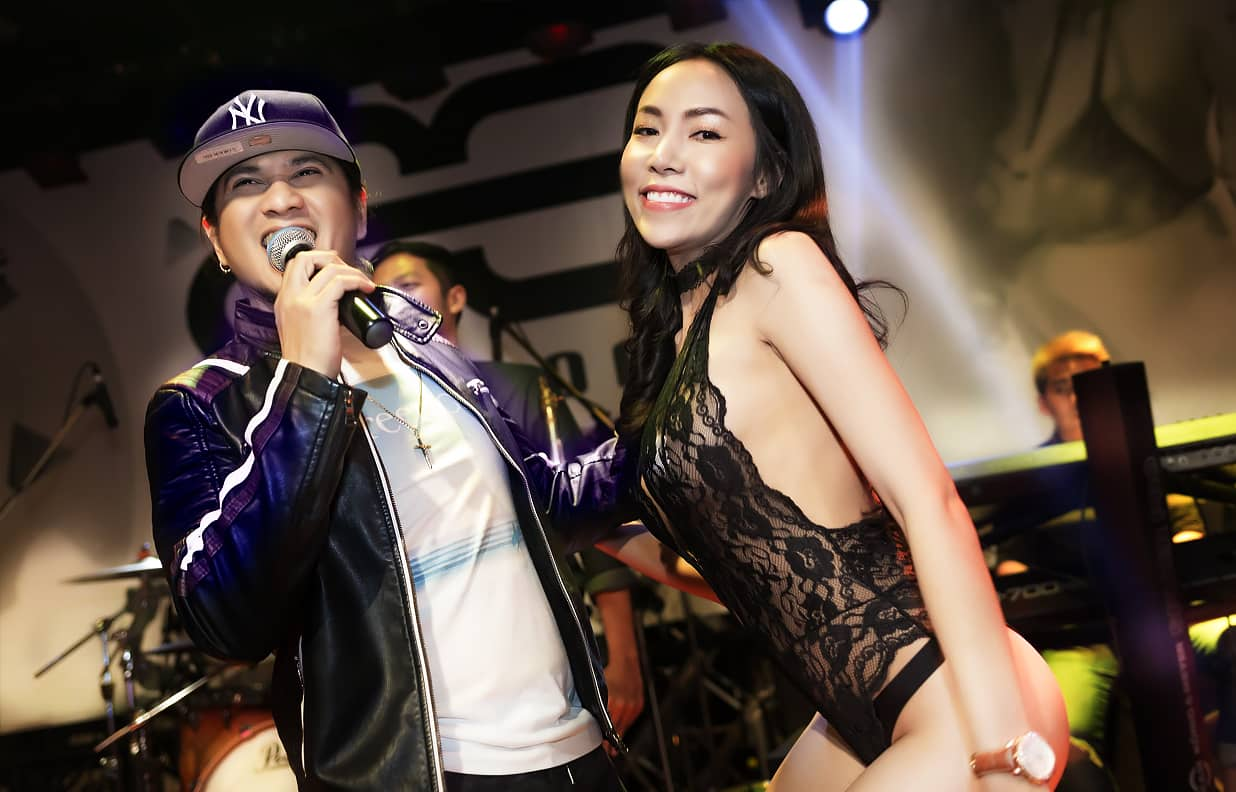 Thai singer next to a sexy Thai girl in black lingerie both performing on stage of the PIMP club room