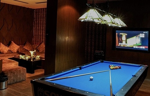 interior of a large private VIP room at The PIMP Bangkok equipped with a flat screen TV pool table and large sofa