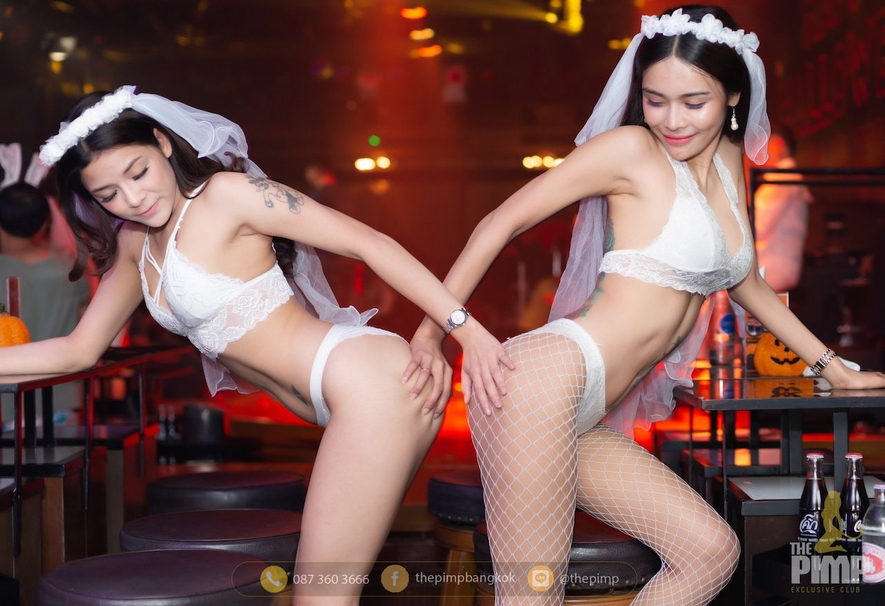 Two Thai girls dressed as sexy brides grabbing each other