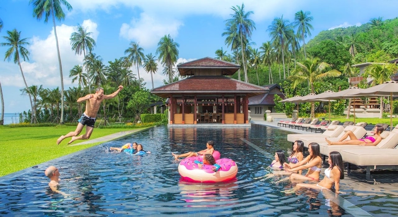 man jumping in a pool at a luxury villa in Thailand