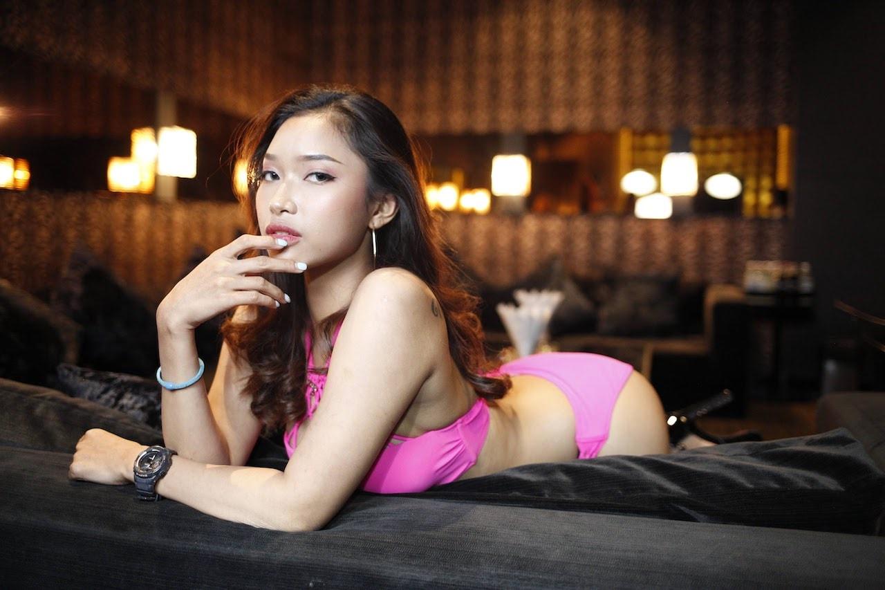 sexy Thai bikini model laying down on the sofa a private VIP room at The PIMP in Bangkok