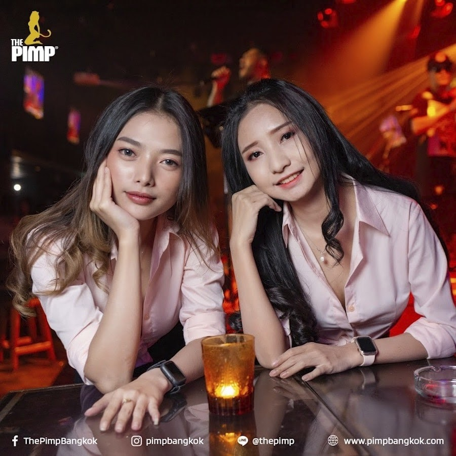 two young cute Thai girls from The PIMP gentlemen club looking straight into the camera