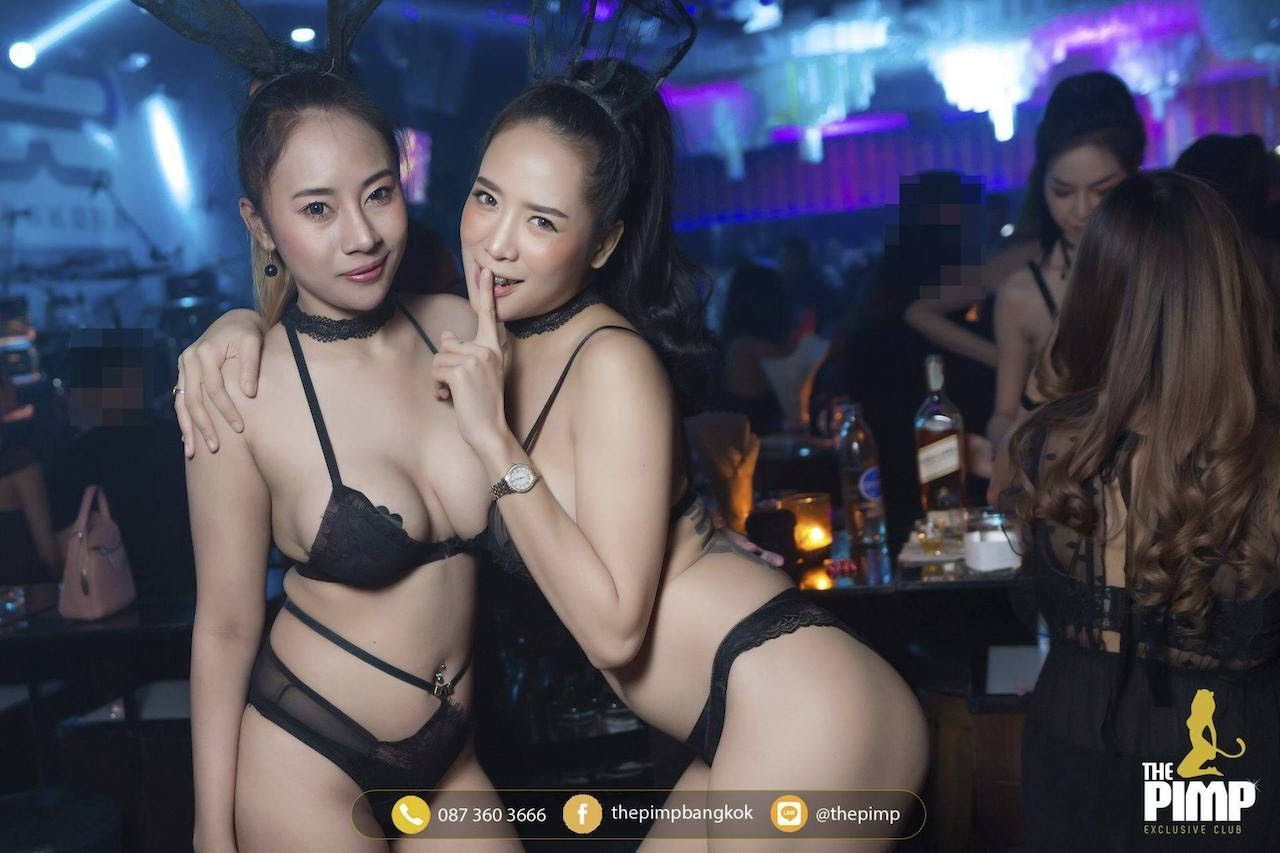two sexy Thai girls in panties giving a naughty look at the camera while people party around them
