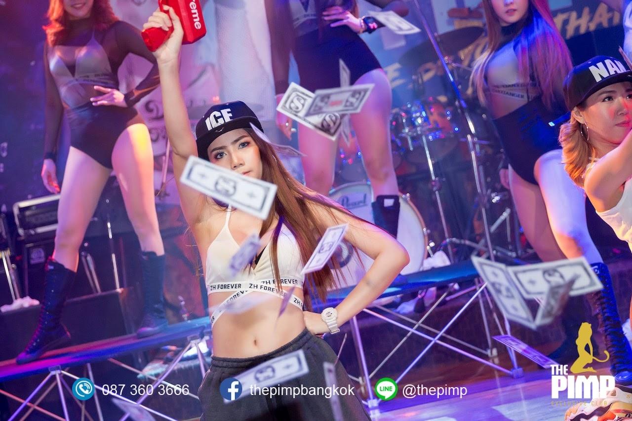 Thai model firing a red cash money gun during a show at a nightclub in Bangkok