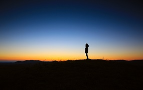 Silhouette of person standing on a hill over dusky skyline
