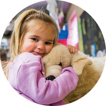 Little girl hugging a stuffed animal at Belchertown Day School