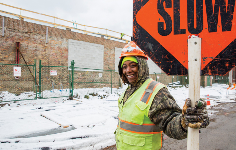 A construction worker directing traffic outside Amped Kitchens