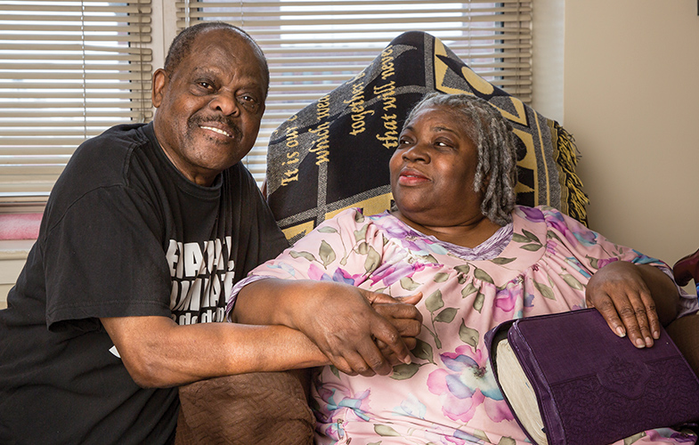 A man and woman holding hands in their home at Emil Jones Senior Housing