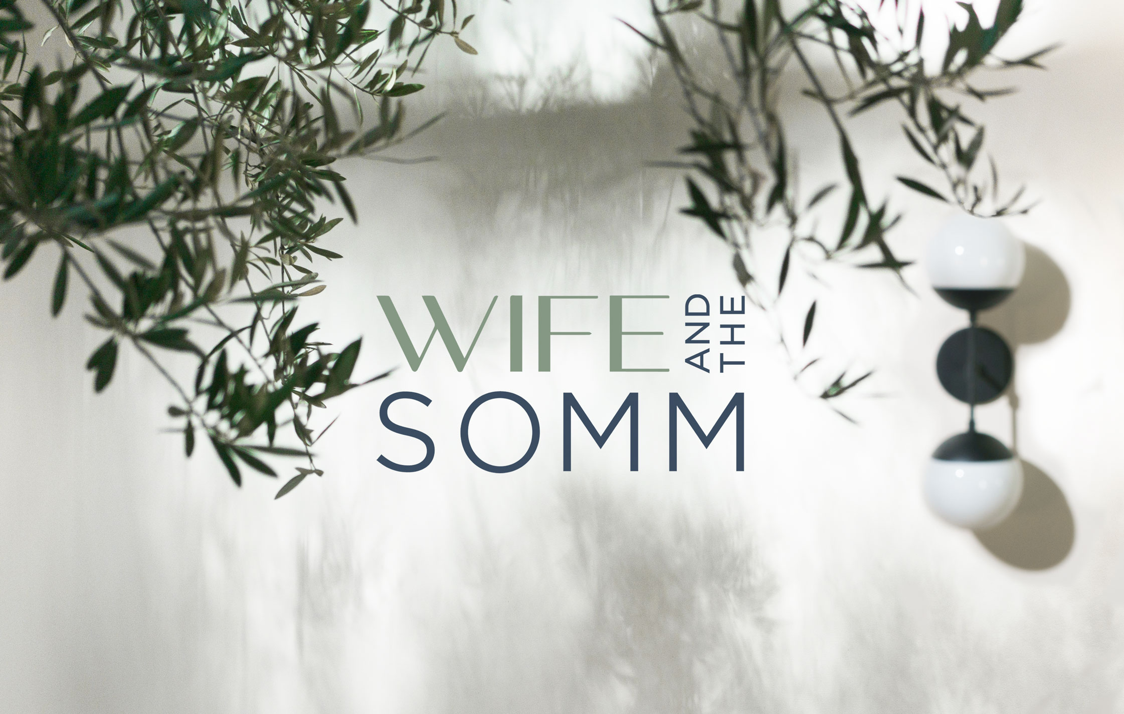 Wife and the Somm logo on beautiful photograph of outdoor dining space with tree leaves in focus.