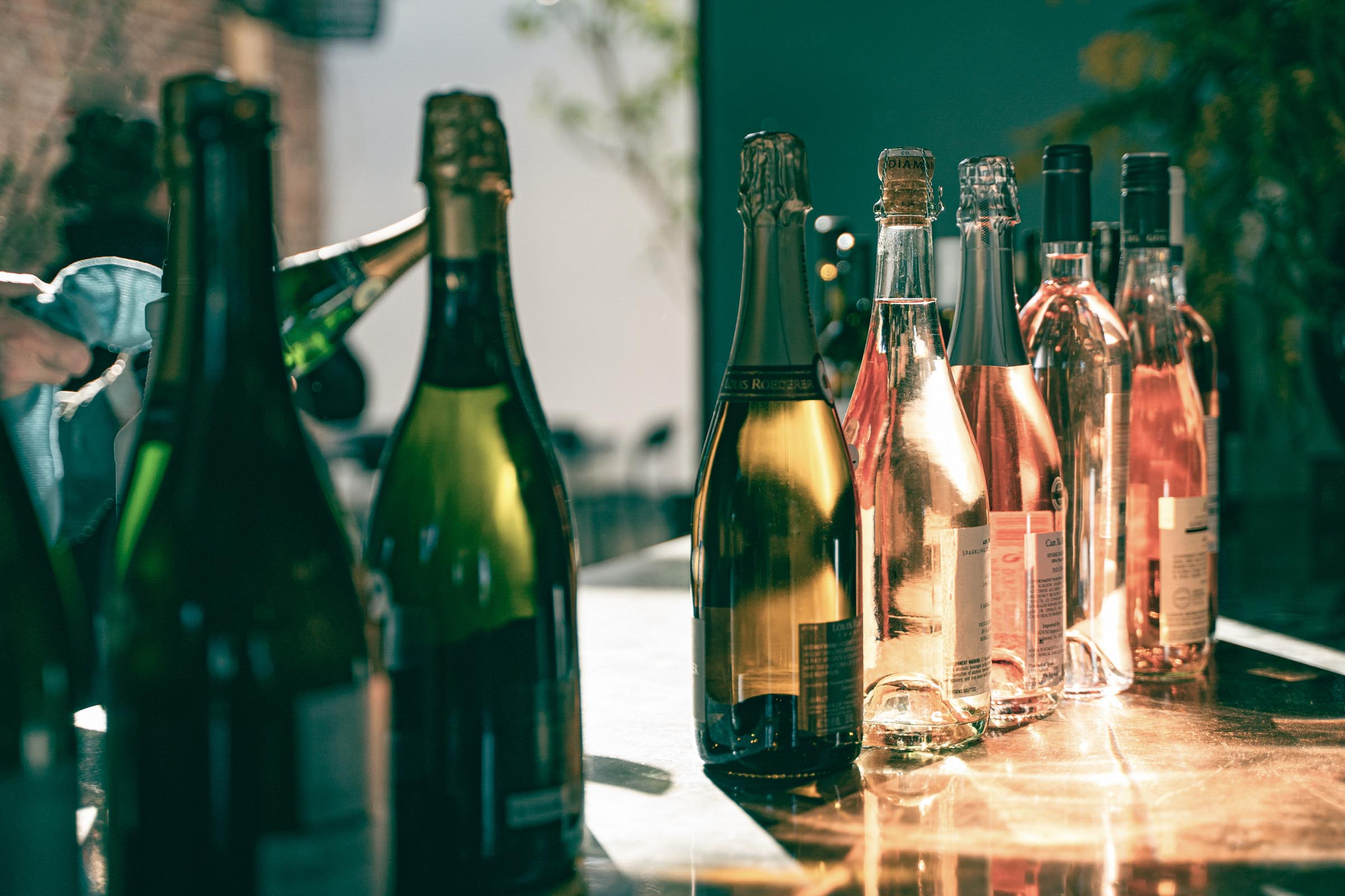 A picture of white wine and rose bottles distributed in a gradient from dark green glass to clear glass.