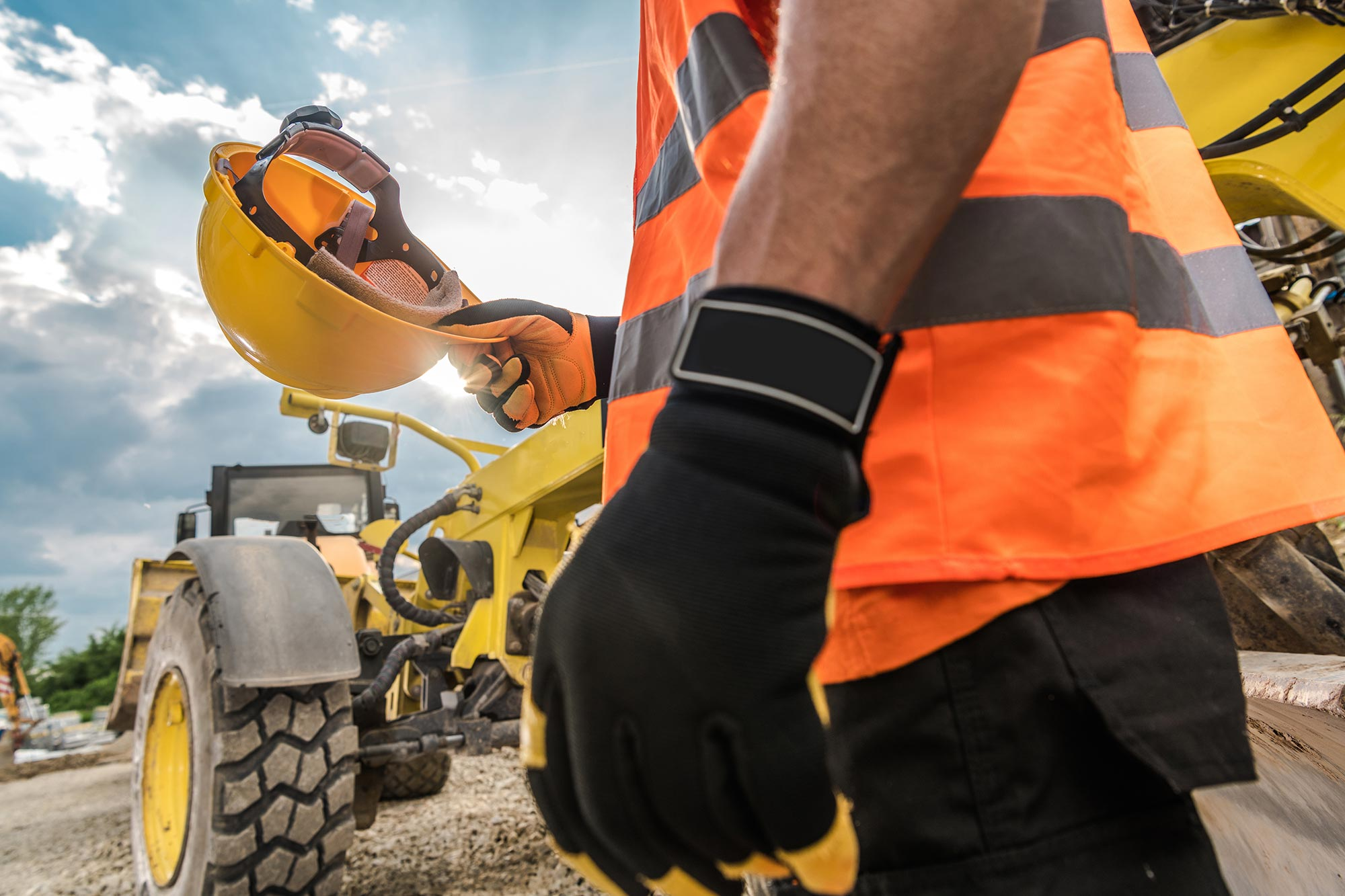 worker with hard hat, hi-vis vest directing equipment