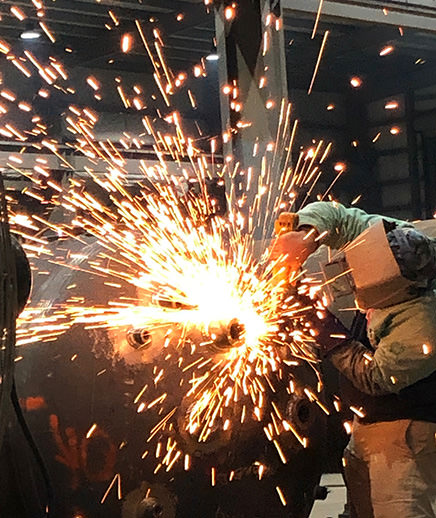 welder actively welding on metal with sparks showing
