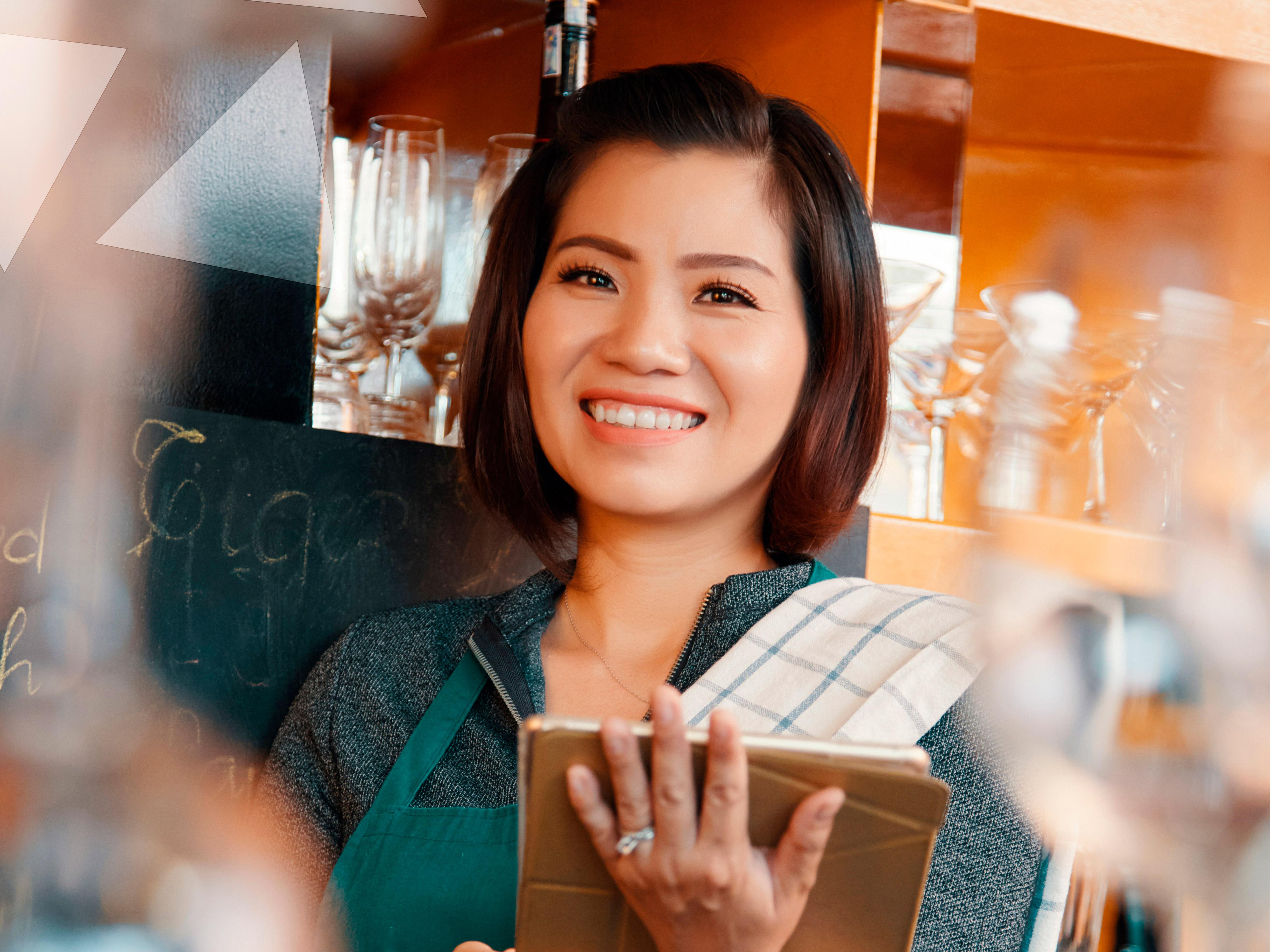 Atendente sorrindo com tablet na mão.