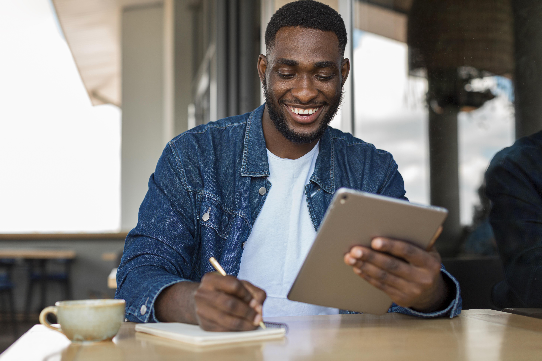 Homem mexendo em tablet e escrevendo.