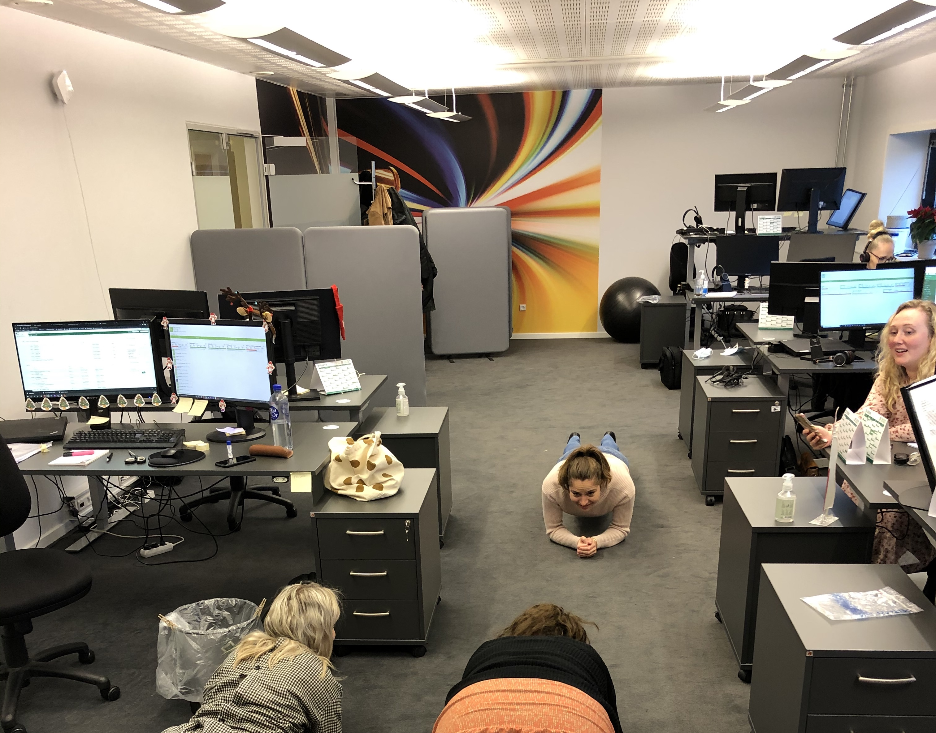 Three women in an office doing the plank