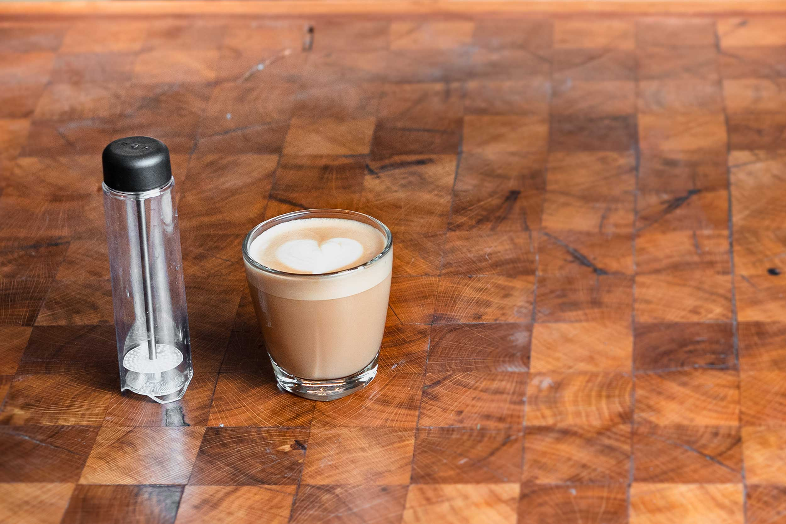 ROK manual milk frother next to coffee with foamed milk on wooden countertop