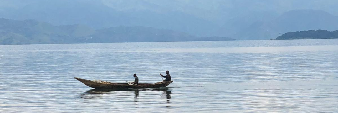 A picture of a lake in the Congo and two fishermen on a boat.
