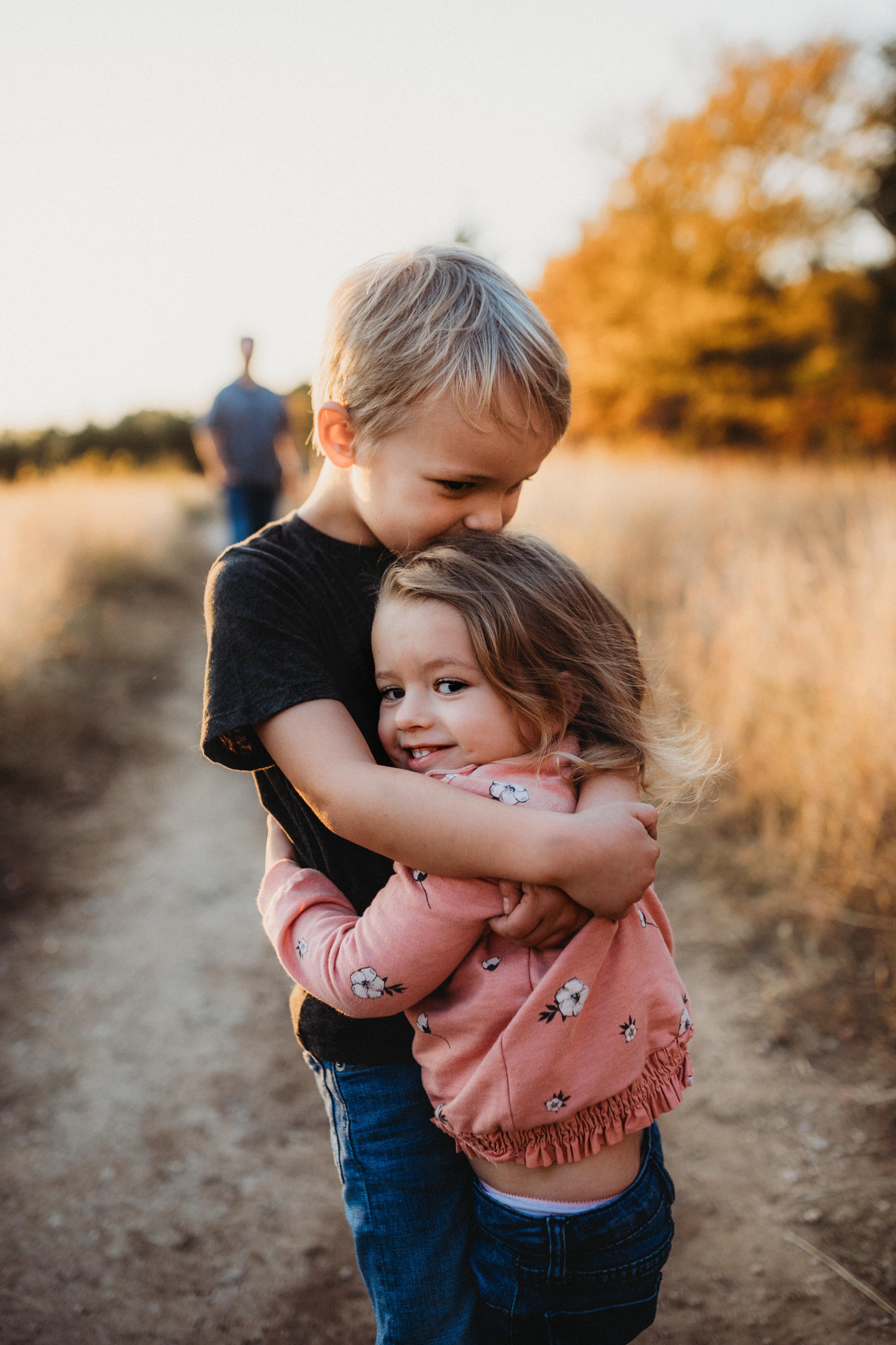 Young siblings hugging in wheat field.
