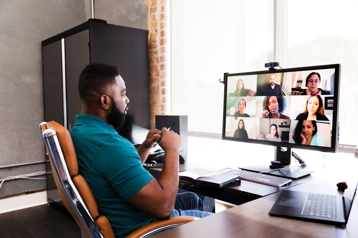 A man holds a virtual meeting with his colleagues.