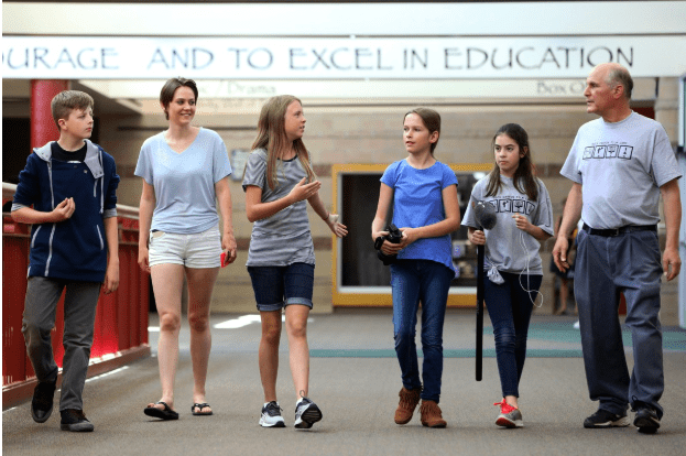 Students and a teacher talk while walking down the school hallway.