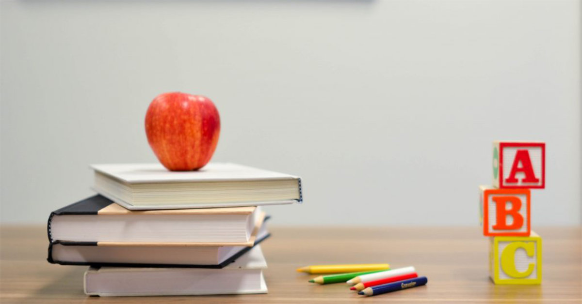 A red apple sits on top of a stack of books with ABC blocks and an array of colored pencils.