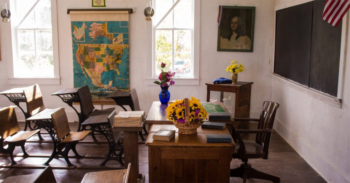 A sunlit classroom is full of empty desks and bouquets of flowers.
