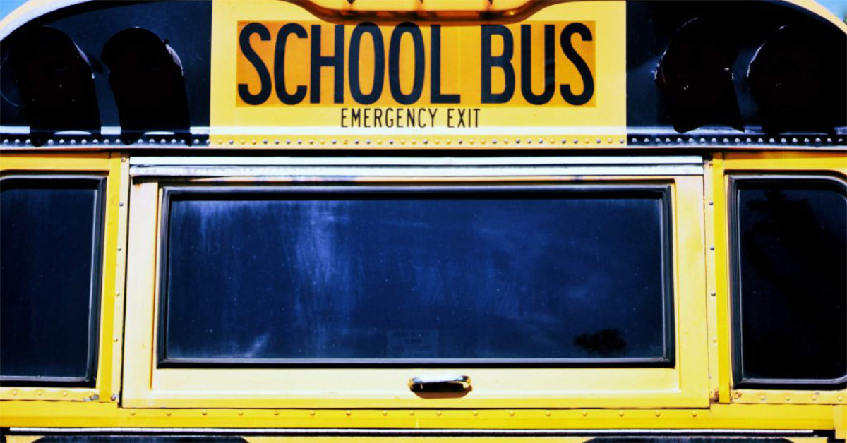 The back of a yellow school bus with an emergency exit.