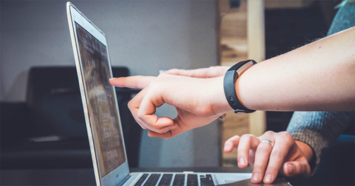 Two people point at the computer screen during online education.