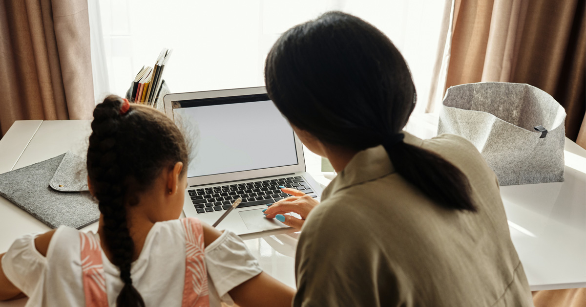 A parent assists a student with remote learning.