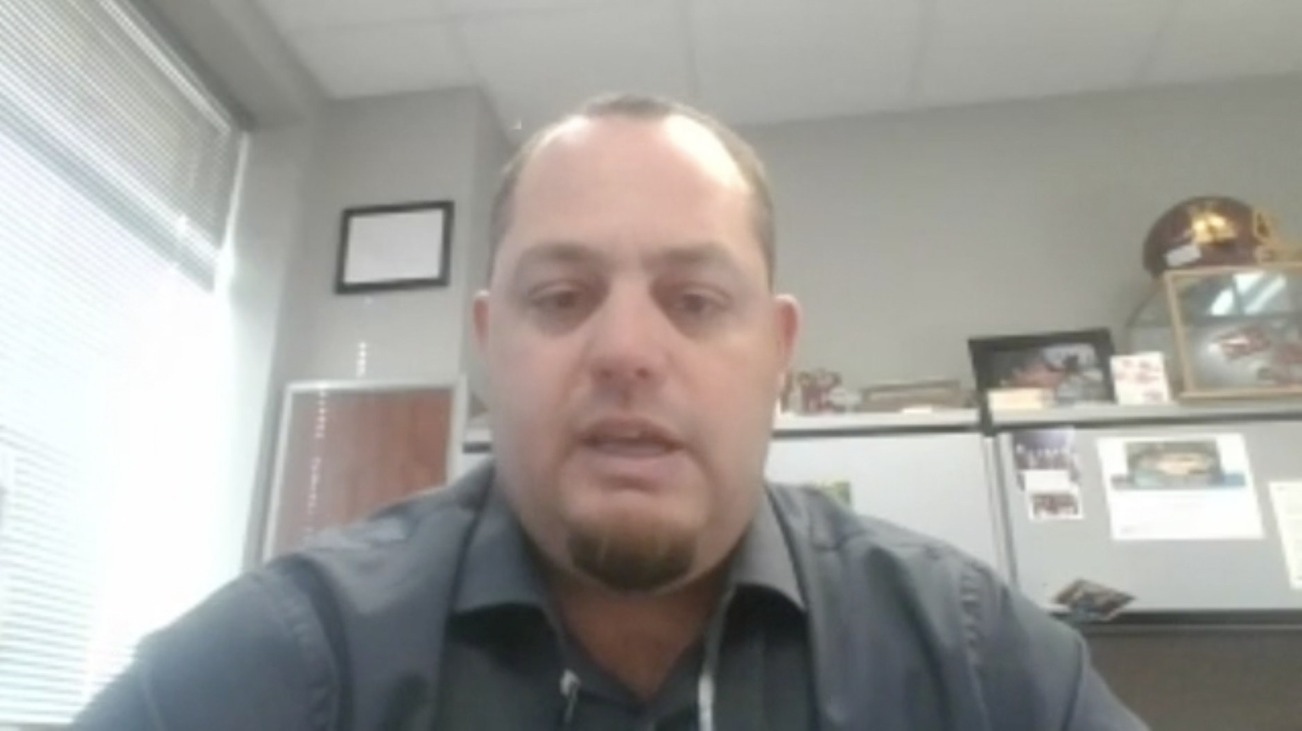 A virtual teacher zooms a lesson from their office.