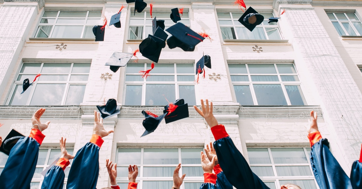 Graduates throw their hats into the air in celebration.