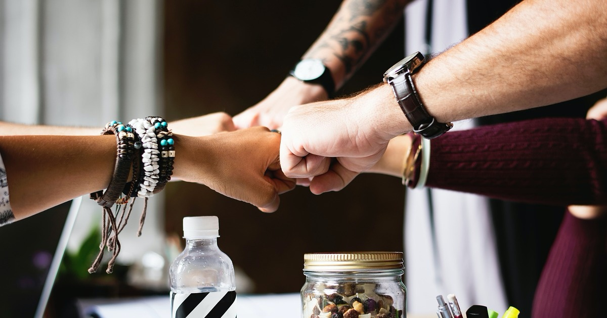 A diverse group of people fist bump in friendship.