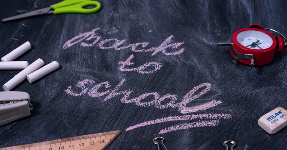 Back to school written on a chalkboard with scattered school supplies